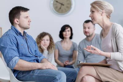 a man sitting in group therapy and listening to the psychologist with concerned family in the back